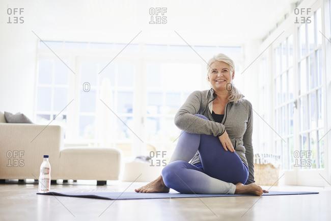 Smiling senior woman doing exercise on mat in living room