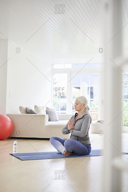 Senior woman with eyes closed meditating in living room