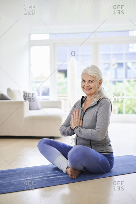 Smiling mature woman with hands clasped meditating in living room