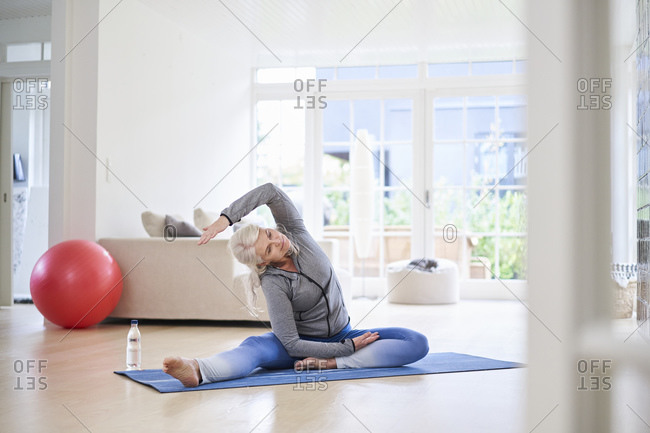 Senior woman stretching arms while exercising in living room