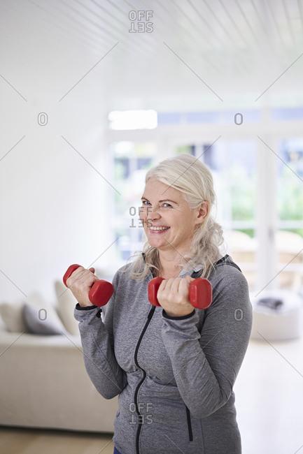 Smiling senior woman lifting dumbbells while exercising at home