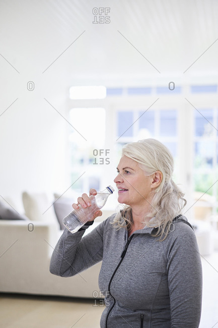 Senior woman contemplating while having water at home