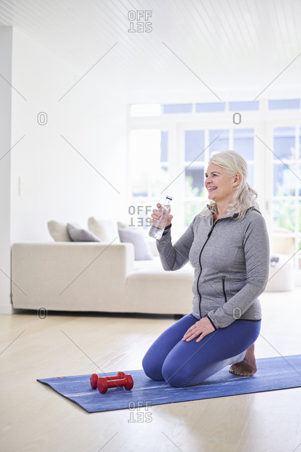 Smiling woman having water while exercising with dumbbells in living room