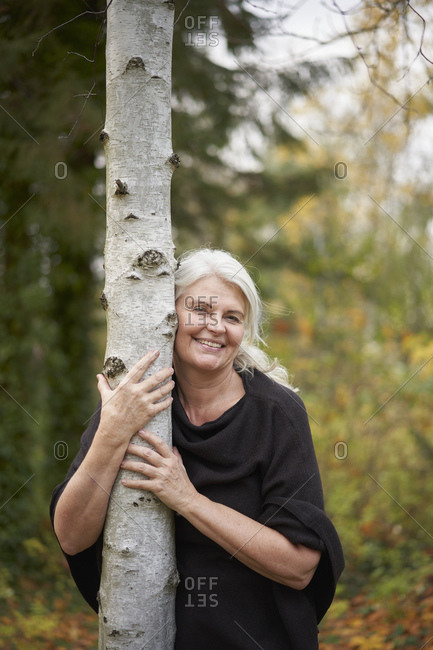 Happy senior woman hugging tree trunk in autumn park