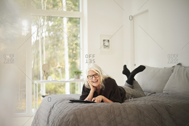Happy senior woman with digital tablet lying on bed in bedroom