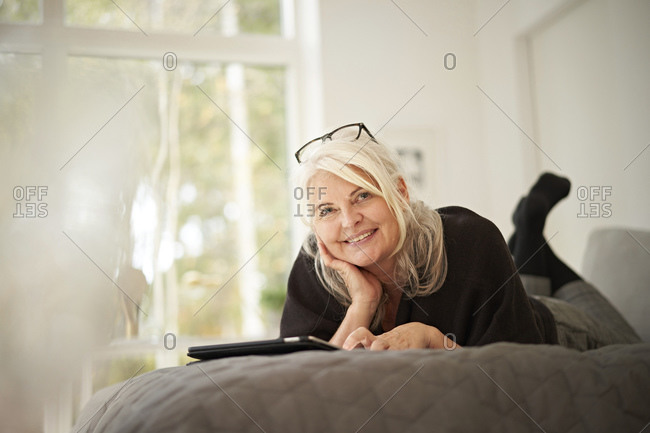 Smiling senior woman with hand on chin lying on bed at home