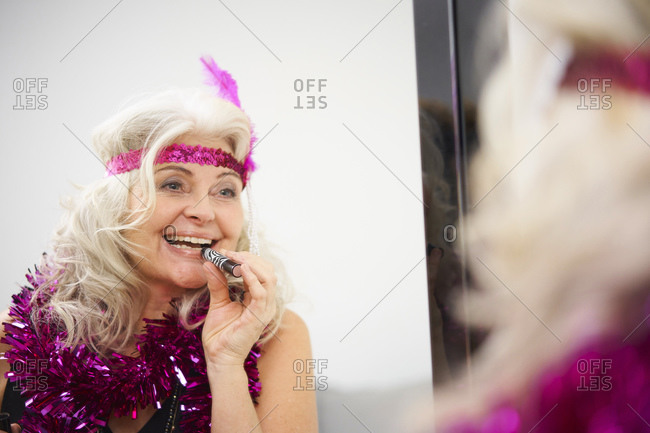 Happy senior woman with garland around neck applying lipstick in front of mirror at home