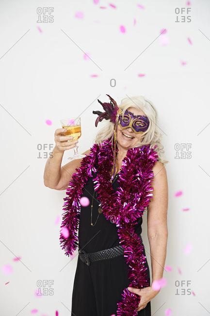 Smiling senior woman enjoying drink while standing against white background