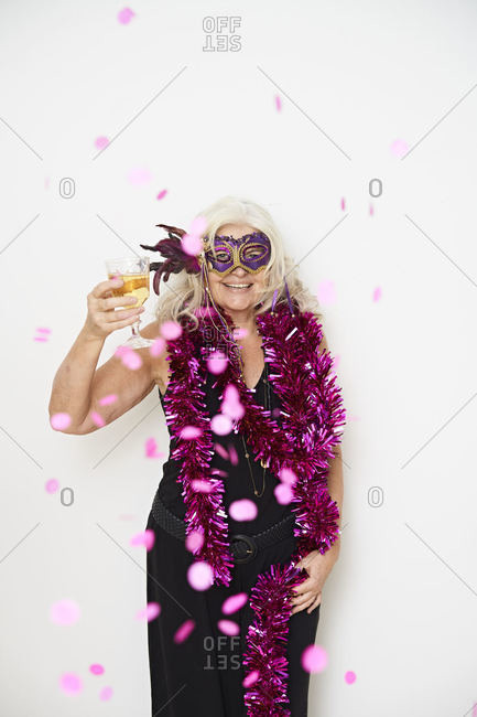 Happy fashionable senior woman with glass wearing masquerade mask against white background