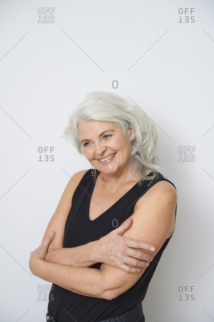 Smiling senior woman hugging herself against white background