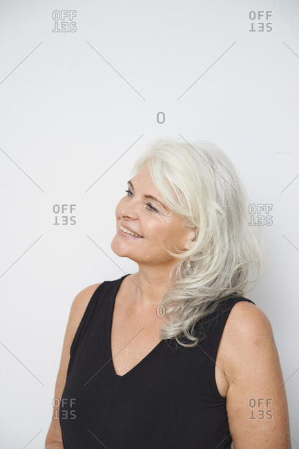Smiling senior woman contemplating against white background