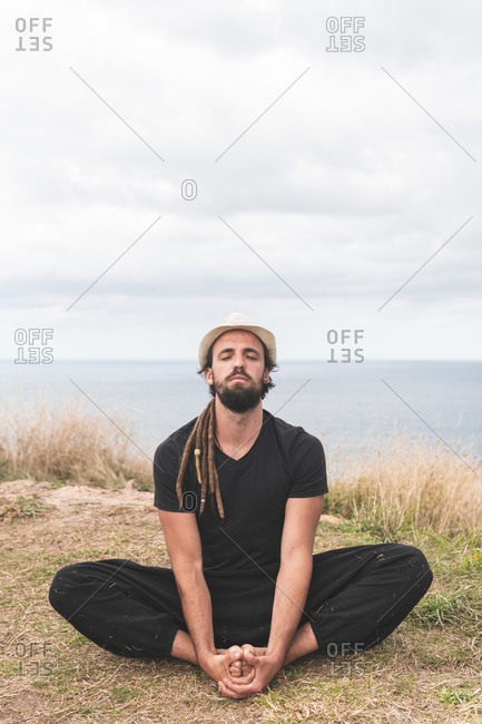 Young man practicing yoga while sitting on field against cloudy sky- Santander- Spain