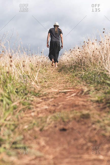 Young man walking in field towards cloudy sky at Santander- Spain