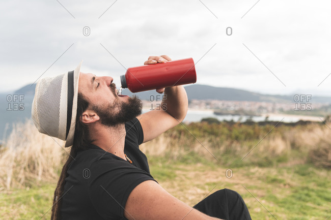 Young man wearing hat drinking water with eyes closed at Santander- Spain