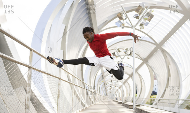 Sportsman with arms outstretched jumping while exercising on walkway