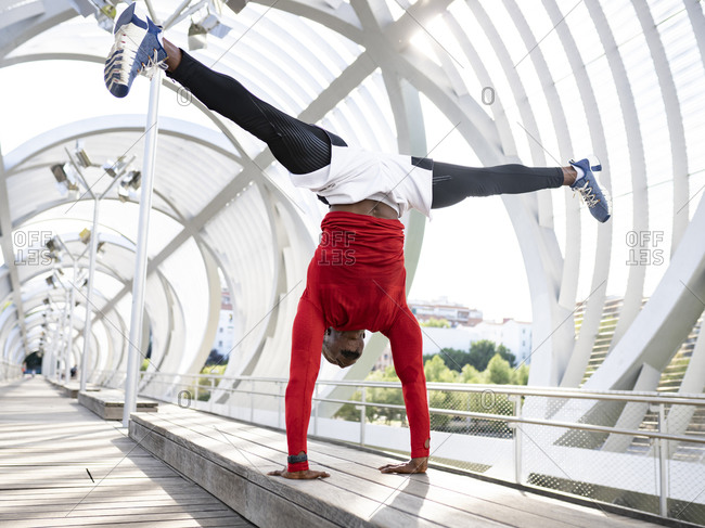 Athlete with stretching leg while practicing handstand on walkway bench