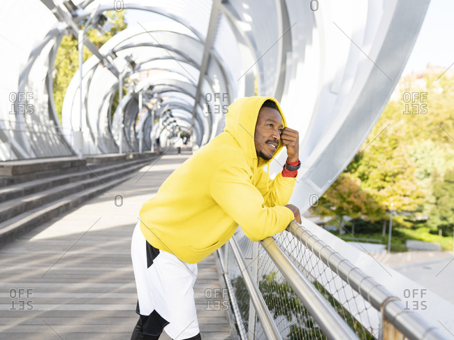 Thoughtful businessman wearing yellow hooded shirt leaning on walkway railing