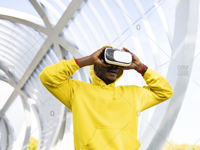 Sportsman using virtual reality headset while standing at elevated walkway