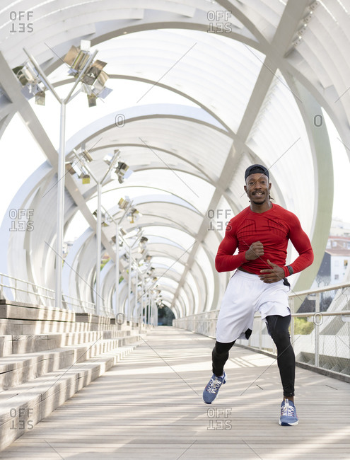 Athlete doing warm up exercise while running on walkway
