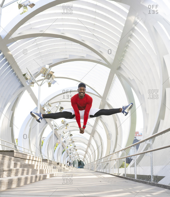 Acrobat jumping while doing the splits on walkway