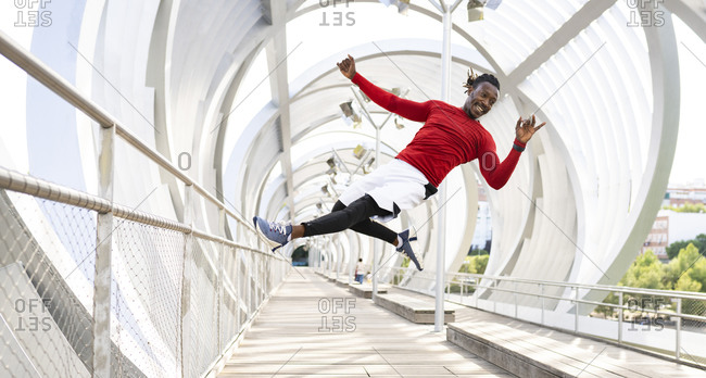 Male athlete exercising while jumping on walkway