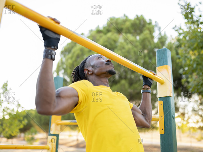 Male athlete doing chin-ups while exercising on road at park