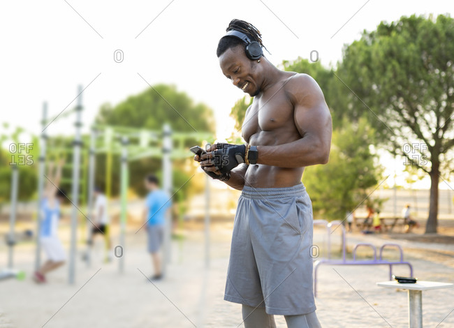 Smiling sportsman wearing headphones using mobile phone while standing at park