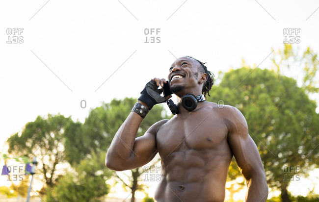 Shirtless sportsman with headphones talking o mobile phone while standing at park