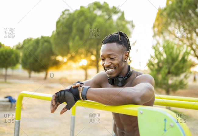 Smiling athlete checking time on wristwatch while standing at park