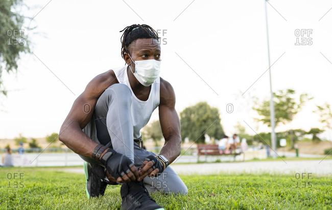 Athlete wearing face mask tying lace of shoe while crouching on ground