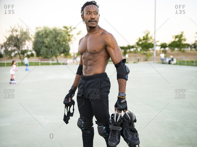 Shirtless athlete holding roller skate shoe while standing at ground