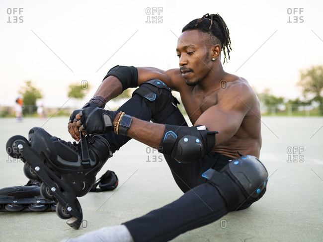 Athlete wearing roller skate while sitting on ground