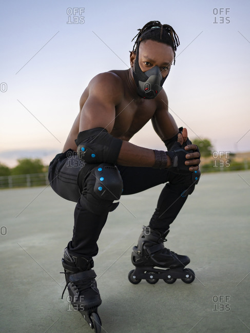 Sportsman wearing protective face mask and roller skate crouching on ground