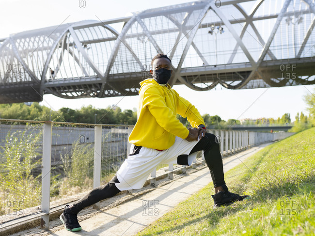 Sportsman looking away while exercising on footpath