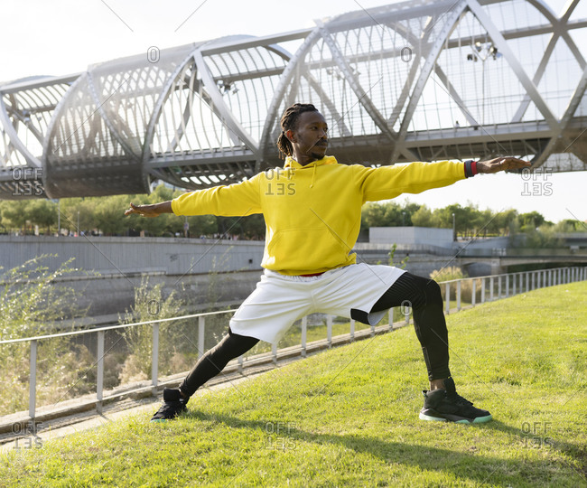 Male athlete practicing warrior pose while exercising against walkway