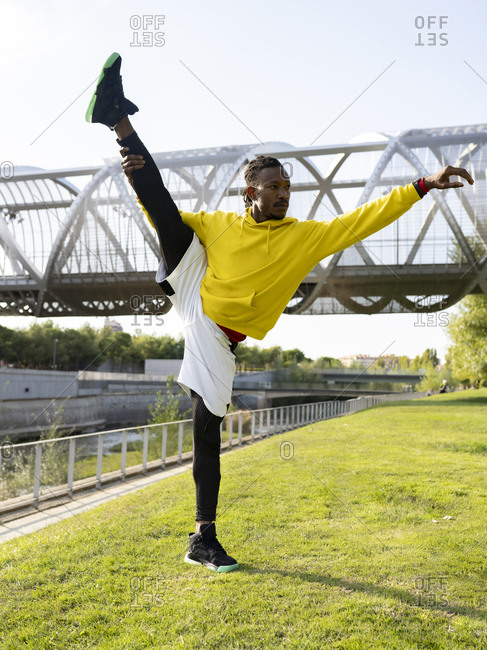 Sportsman doing splits yoga while standing against walkway