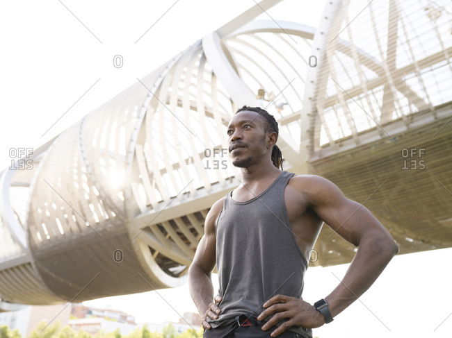 Muscular build athlete with hand on hip looking away while standing against walkway