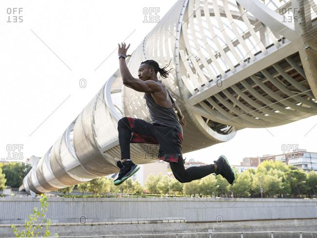 Male sportsman running against walkway