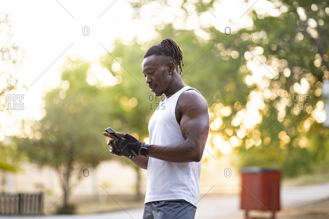 Sportsman using mobile phone while standing outdoors