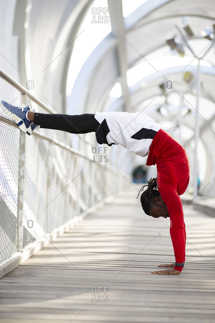 Athlete doing handstand while exercising on walkway