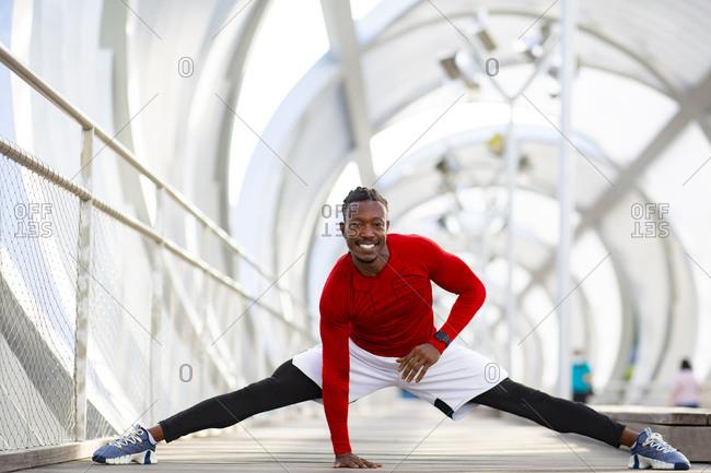 Smiling athlete doing splits while exercising on walkway
