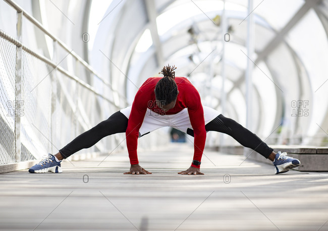 Male athlete practicing splits while exercising on walkway