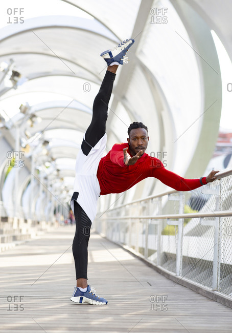 Sportsman stretching while doing splits standing on walkway