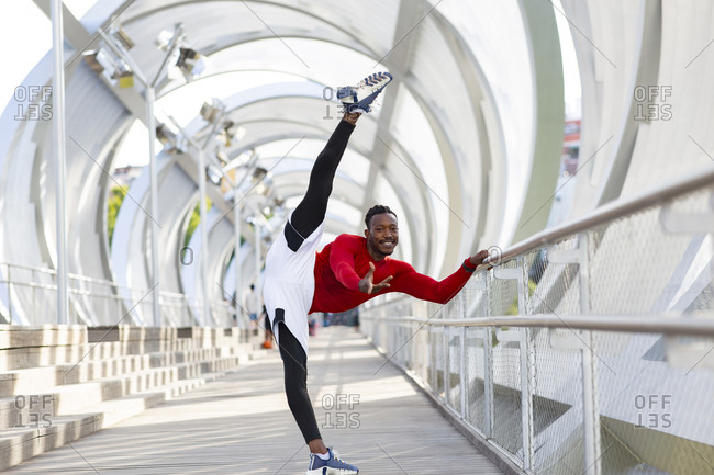 Smiling sportsman exercising while doing the splits on walkway