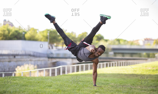 Smiling athlete pointing while doing handstand outdoors