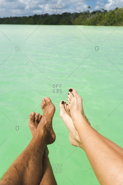 Heterosexual couple legs over ocean on sunny day