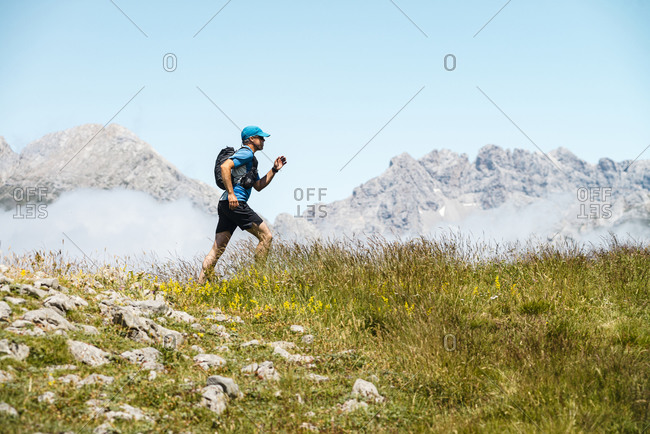 Mature sportsman trail running in the mountains on meadow against blue sky
