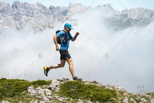 Mature sportsman trail running through foggy mountains