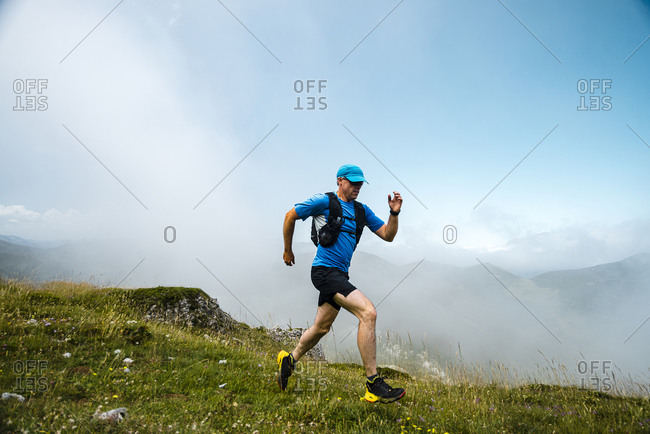 Mature sportsman trail running in the mountains on meadow