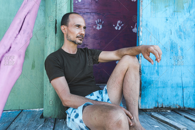Mature man contemplating while leaning on doorway of beach hut